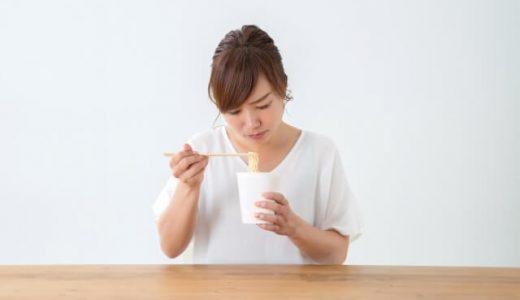 カップ麺を食べる女性
